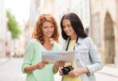 Adolescentes sonrientes con el mapa y la cámara Foto de archivo libre de regalías