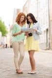 Adolescentes sonrientes con el mapa y la cámara Fotografía de archivo libre de regalías