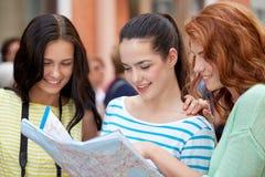 Adolescentes sonrientes con el mapa y la cámara al aire libre Imagen de archivo libre de regalías