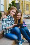 Adolescentes sonrientes con el ordenador de la PC de la tableta al aire libre Imagenes de archivo