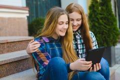 Adolescentes sonrientes con el ordenador de la PC de la tableta al aire libre Imágenes de archivo libres de regalías