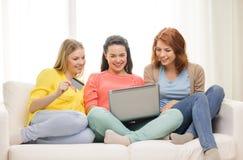 Adolescentes sonrientes con el ordenador portátil y la tarjeta de crédito Foto de archivo libre de regalías