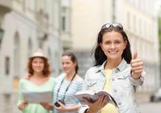 Adolescentes sonrientes con la guía y la cámara de la ciudad Imagen de archivo libre de regalías