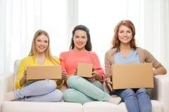 Adolescentes sonrientes con las cajas de cartón en casa Imagenes de archivo