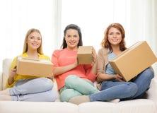 Adolescentes sonrientes con las cajas de cartón en casa Foto de archivo libre de regalías