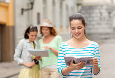 Adolescentes sonrientes con las guías y la cámara de la ciudad Foto de archivo libre de regalías