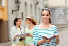 Adolescentes sonrientes con las guías y la cámara de la ciudad Imagen de archivo