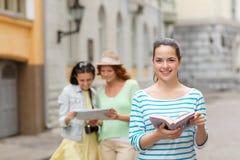 Adolescentes sonrientes con las guías y la cámara de la ciudad Fotografía de archivo