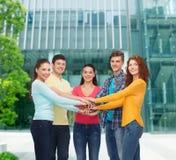 Adolescentes sonrientes con las manos encima de uno a Fotos de archivo