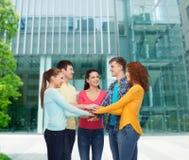 Adolescentes sonrientes con las manos encima de uno a Imagen de archivo libre de regalías