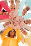 Adolescentes sonrientes con las manos encima de uno a Foto de archivo