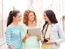 Adolescentes sonrientes con PC y la cámara de la tableta Imágenes de archivo libres de regalías