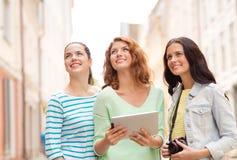 Adolescentes sonrientes con PC y la cámara de la tableta Fotografía de archivo libre de regalías