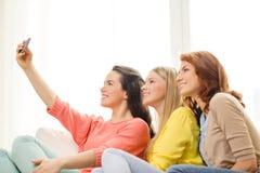 Adolescentes sonrientes con smartphone en casa Foto de archivo libre de regalías
