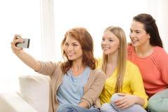 Adolescentes sonrientes con smartphone en casa Fotografía de archivo