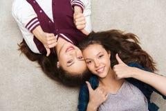 Adolescentes sonrientes en el piso que muestra los pulgares para arriba Foto de archivo libre de regalías