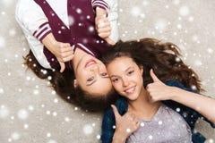 Adolescentes sonrientes en el piso que muestra los pulgares para arriba Imagen de archivo