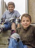 Adolescentes sonrientes en equipos de la protección del rodillo-perfilado Imágenes de archivo libres de regalías