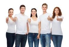 Adolescentes sonrientes en las camisetas que muestran los pulgares para arriba Fotografía de archivo