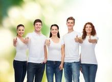 Adolescentes sonrientes en las camisetas que muestran los pulgares para arriba Foto de archivo libre de regalías