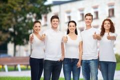 Adolescentes sonrientes en las camisetas que muestran los pulgares para arriba Imagen de archivo