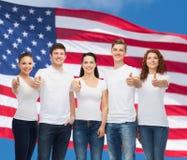 Adolescentes sonrientes en las camisetas que muestran los pulgares para arriba Imágenes de archivo libres de regalías