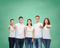 Adolescentes sonrientes en las camisetas que muestran los pulgares para arriba Foto de archivo