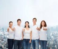 Adolescentes sonrientes en las camisetas que muestran los pulgares para arriba Fotos de archivo