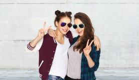 Adolescentes sonrientes en las gafas de sol que muestran paz Fotos de archivo libres de regalías