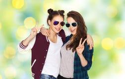 Adolescentes sonrientes en las gafas de sol que muestran paz Imagenes de archivo