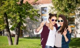 Adolescentes sonrientes en las gafas de sol que muestran paz Fotografía de archivo libre de regalías