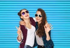 Adolescentes sonrientes en las gafas de sol que muestran paz Foto de archivo