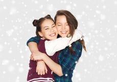 Adolescentes sonrientes felices que abrazan sobre nieve Foto de archivo