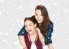 Adolescentes sonrientes felices que abrazan sobre nieve Fotografía de archivo