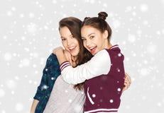 Adolescentes sonrientes felices que abrazan sobre nieve Imagen de archivo