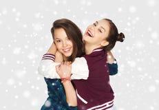 Adolescentes sonrientes felices que abrazan sobre nieve Fotografía de archivo libre de regalías