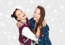 Adolescentes sonrientes felices que abrazan sobre nieve Imágenes de archivo libres de regalías