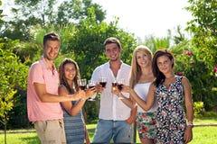 Adolescentes sonrientes felices que beben el vino rojo Imagenes de archivo