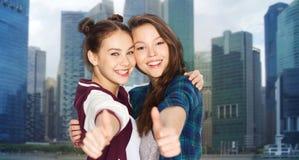 Adolescentes sonrientes felices que muestran los pulgares para arriba Imagen de archivo