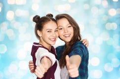 Adolescentes sonrientes felices que muestran los pulgares para arriba Imagenes de archivo
