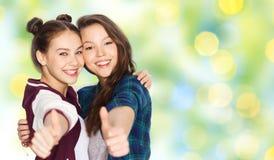 Adolescentes sonrientes felices que muestran los pulgares para arriba Foto de archivo libre de regalías