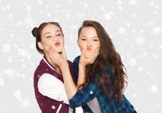 Adolescentes sonrientes felices que se divierten sobre nieve Fotografía de archivo