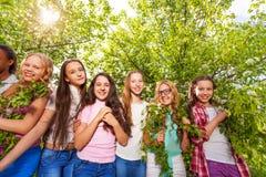 Adolescentes sonrientes que colocan y que sostienen bancos Imagen de archivo