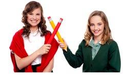 Adolescentes sonrientes que hacen la muestra cruzada con el lápiz Fotografía de archivo libre de regalías