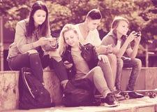 Adolescentes sonrientes que juegan con los teléfonos móviles Fotografía de archivo libre de regalías