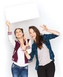 Adolescentes sonrientes que llevan a cabo al tablero en blanco blanco Foto de archivo