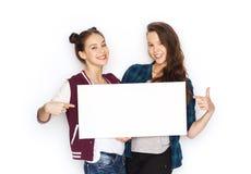 Adolescentes sonrientes que llevan a cabo al tablero en blanco blanco Imagen de archivo