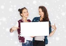Adolescentes sonrientes que llevan a cabo al tablero en blanco blanco Imagenes de archivo