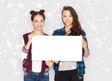 Adolescentes sonrientes que llevan a cabo al tablero en blanco blanco Imagen de archivo libre de regalías