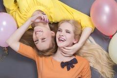 Adolescentes sonrientes que mienten con los globos coloridos Imagen de archivo